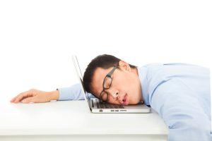 疲れてパソコンに伏せる男性